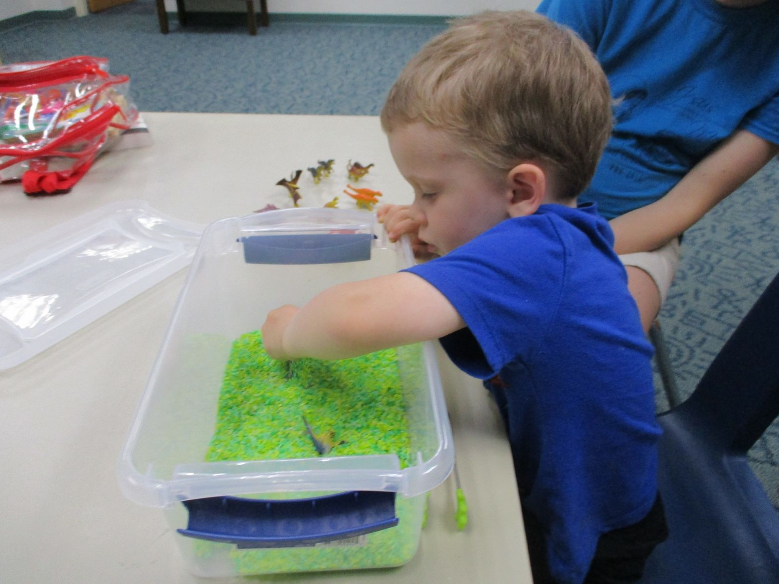 A boy digs for toys in a sensory bin of green rice.
